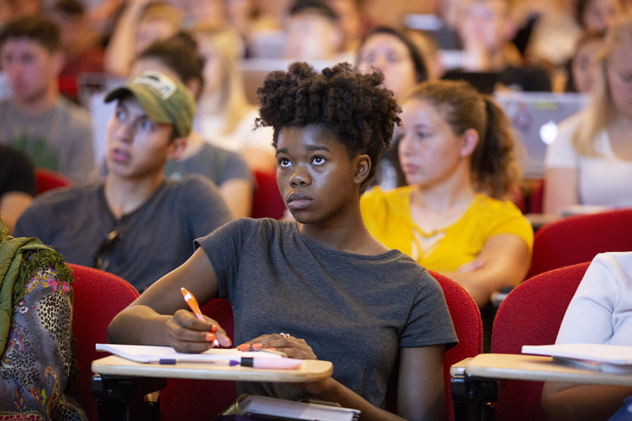 A student takes notes in the front row of a large lecture class.